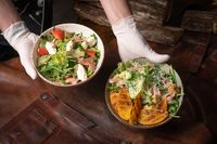 Two bowls of vegetable salad with salmon, mozzarella cheese and grilled slices of fruits stands on a table covered with a leather rag. Restaurant concept. Vertical image