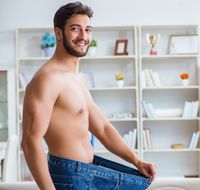 Man in oversized pants in weight loss concept