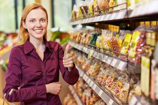 Junge Frau im Supermarkt hält Daumen hoch