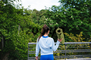 Young woman walking in urban park holding fitness rug.