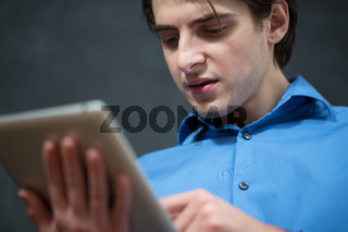 Cheerful smiling man receiving good news on tablet with fist raised