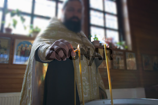 Orthodox priest is preparing for the rite of baptism. A church attendant lights the candles.