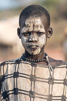 MUNDARI TRIBE, SOUTH SUDAN - MARCH 11, 2020: Teenager in traditional garment and with face painted with mud while living in Mundari Tribe village in South Sudan, Africa