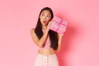 Holidays, celebration and lifestyle concept. Excited and intrigued cute asian girl, celebrating birthday, receive wrapped gift and wonder whats inside, shaking box to guess what present friend gave