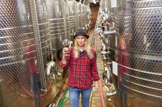 Frau als Winzer Azubi mit einem Glas Rotwein