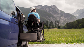 man on wheelchair going out of a car on electric lift specialized vehicle for people with disabilities. Self help for disabled people concept