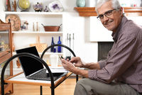 Mature man working from home with his laptop and cell phone. Man is looking at the samera ans smilin