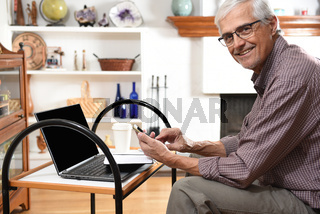 Mature man working from home with his laptop and cell phone. Man is looking at the samera ans smiling.
