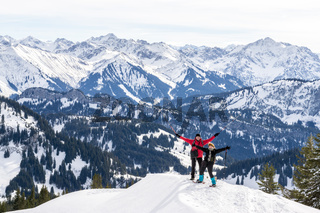 Senior couple is snowshoe hiking in alpine snow winter mountains panorama. Happy successful People with raised arms. Allgau, Bavaria, Germany.