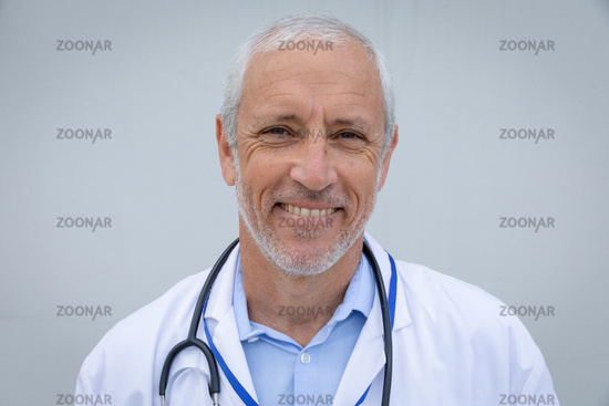 Portrait of senior male doctor smiling against grey background
