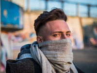 Man with scarf on face resting on street
