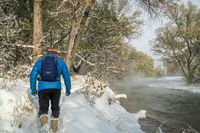 senior male is hiking along river in snow