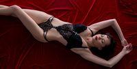 Woman posing in bodysuit lying on velvet bed sheet