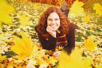 Young woman lying on a lawn surrounded by falling autumn leaves. Fall, seasonal and autumnal concept