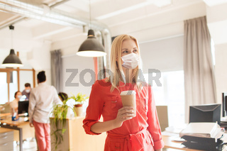 female office worker in mask with coffee cup