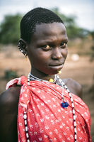 TOPOSA TRIBE, SOUTH SUDAN - MARCH 12, 2020: Teenager with short hair wearing bright garment and accessories and looking at camera on blurred background of Toposa Tribe village in South Sudan, Africa