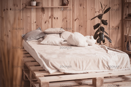 Cozy bed with pillows and bear toy in wooden home interior