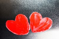 Two red painted hearts on metal