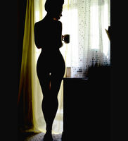 Dark silhouette of woman against window, slim young female with long hair seated on bed alone in bedroom holding morning tea cup