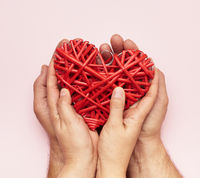 two female hands lie in male palms and hold a red heart on a pink background