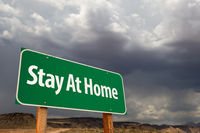 Stay At Home Green Road Sign Against An Ominous Cloudy Sky