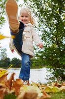 Mädchen spielt im Herbst mit Blättern