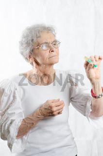 alte Frau schaut Spritze an