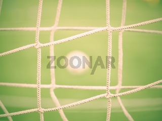 View through football gate net. Soccer ball on green grass
