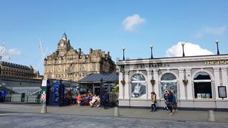 Bahnhof und Straßencafé auf der Waverley Brücke in Edinburgh, im Hintergrund das historische Balmoral Hotel