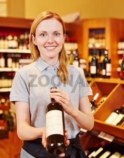 Sommelier im Weinhandel empfiehlt Flasche Wein
