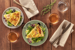 Slices of French quiche with salmon, with green salad leaves, thyme and white wine, shot from the top on a rustic wooden background