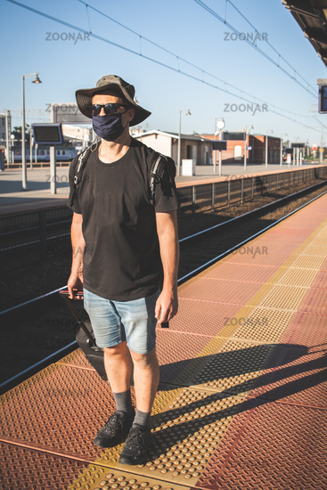 Man with a mask waiting for a train during Covid19 pandemic