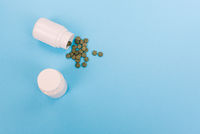 Green pills from a white bottle. Pills spilling out of a bottle on a blue background. Small white plastic jars with pills on a medical background.