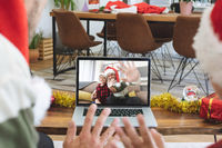 Rear view of man and son in santa hats waving while having a videocall with man and son in santa hat