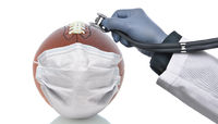 Covid-19 and Sports Concept. An American Football With Surgical Mask and a doctors hand holding a st