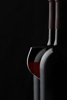 A glass of red wine between two bottles against a black background