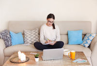 Female freelancer using smartphone at home
