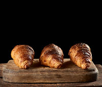 baked croissants on brown kitchen board, black background