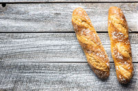 Two crispy fresh baguettes on wooden table.