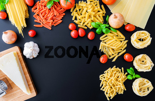 different italian pasta noodles on dark background with basil leaves, fresh tomatoes, onions, parmesan cheese and grater