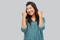 happy asian woman celebrating success over grey