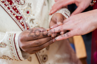 Indian groom putting ring on a brides hand