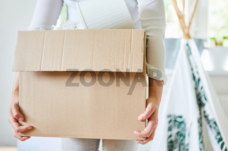 Frau trägt einen Umzugskarton beim Einzug