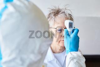 Fieber messen in Schutzkleidung bei Covid-19 Patientin