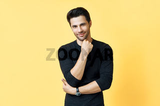 Smiling thoughtful man portrait on yellow background