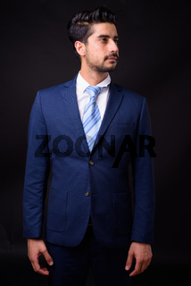 Young handsome bearded Persian businessman against black background