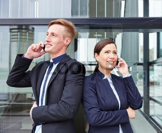 Zwei Geschäftsleute telefonieren mit Smartphone