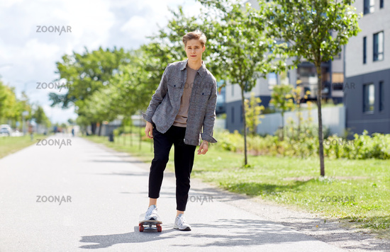 teenage boy on skateboard on city street