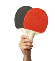 female hand holds two wooden table tennis rackets