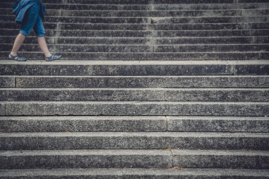 Legs of a woman walking between concrete stairs